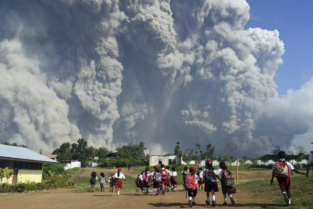 Alunos de escola passeiam em meio à erupção do vulcão Sinabung, na Indonésia