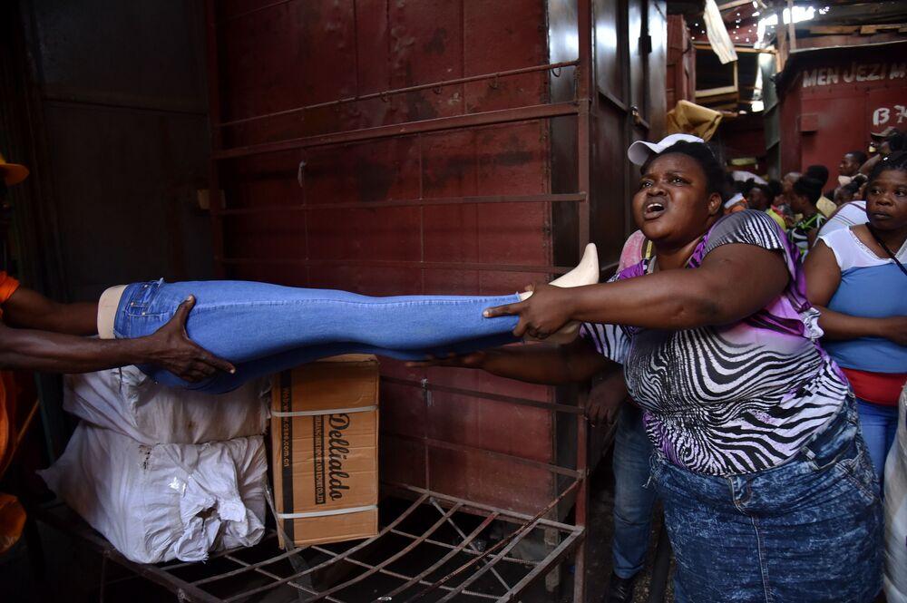 Vendedores tentam salvar seus artigos comerciais do incêndio na cidade de Porto Príncipe, no Haiti