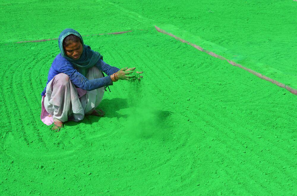 Mulher indiana prepara pó colorido nas vésperas do festival tradicional de Holi, na Índia