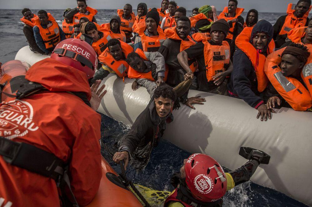 Membros da organização Proactiva Open Arms salvam imigrantes que saíram da Líbia para alcançar o solo europeu