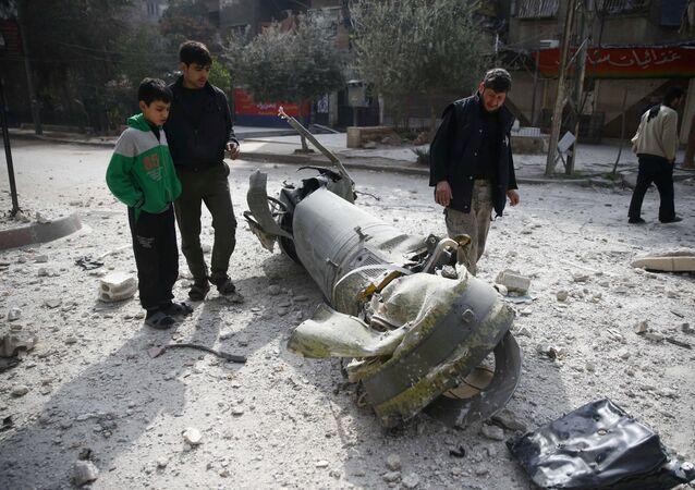 Transeuntes observam restos de mísseis na cidade sitiada de Douma, no leste de Ghouta, em Damasco, Síria, 23 de fevereiro de 2018