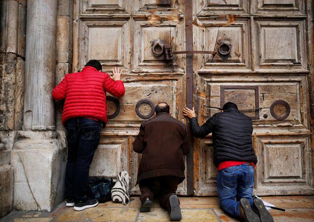 Fiéis se ajoelham e rezam em frente às portas fechadas da Igreja do Santo Sepulcro na Cidade Velha de Jerusalém, 25 de fevereiro de 2018
