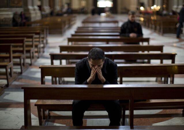 Padre reza dentro da Igreja de Santo Inácio de Loyola, em Roma, 14 de março de 2013