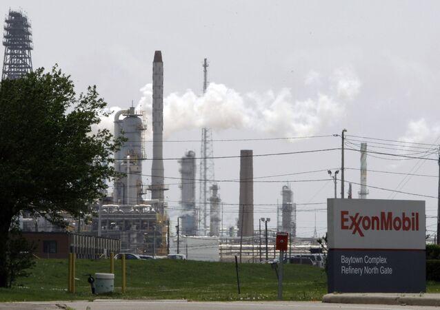 Nesta foto de arquivo de 16 de abril de 2010, o vapor sobe das torres em uma refinaria da Exxon Mobil em Baytown, no Texas