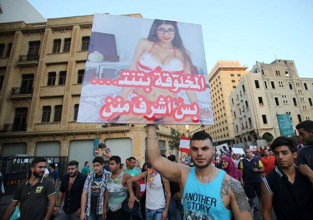 """Ativista com cartaz de atriz pornô de origem libanesa, Mia Khalifa, dizendo """"é verdade que esta mulher faz sexo, mas ela é mais decente do que eles"""" durante protesto contra políticos em Beirut, Líbano (foto de arquivo)"""