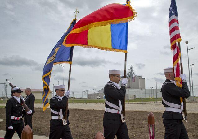Portadores da bandeira da Marinha dos EUA, celebrando a inauguração de uma base de defesa de mísseis, em Deveselu. Da cerimônia de abertura participaram autoridades oficias dos EUA, OTAN e Romênia em uma base originalmente estabelecida pela União Soviética em Deveselu, no sul da Romênia, 12 de maio de 2016. A base de defesa de mísseis dos EUA na Romênia, visando proteger a Europa das ameaças de mísseis balísticos, foi declarada operacional na quinta-feira, provocando a ira da Rússia que alegou ter um sistema militar avançado em sua antiga área de influência (AP Photo/Vadim Ghirda)