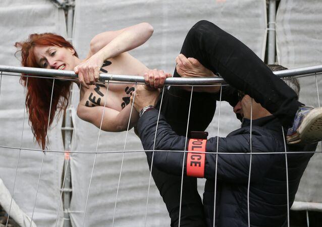 Polícial agarra ativista do FEMEN que protesta contra partido de Marin Le Pen, na França