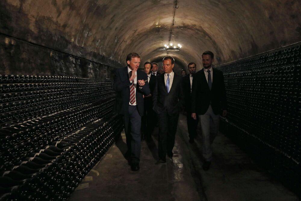 Premiê russo, Dmitry Medvedev (C) observa as caves da empresa Abrau Durso. À direita está o presidente do conselho de diretores da empresa Abrau Durso, Pavel Titov. À esquerda – o delegado da Presidência da Rússia para defesa dos direitos dos empresários, Boris Titov, maio de 2014