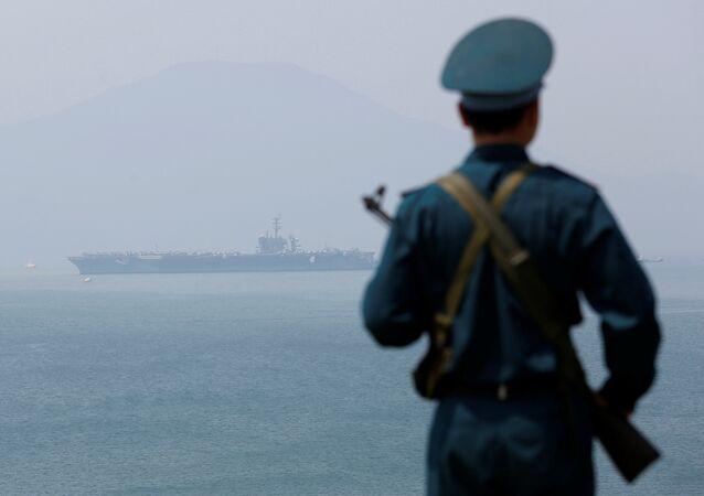 Soldado vietnamita e o porta-aviões USS Carl Vinson ao fundo. Foto de março de 2018.