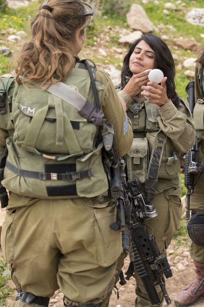 Soldadas israelenses do batalhão misto Lions of the Jordan (Leões da Jordânia) limpam seu rosto após participarem do treinamento final antes de receber seu posto