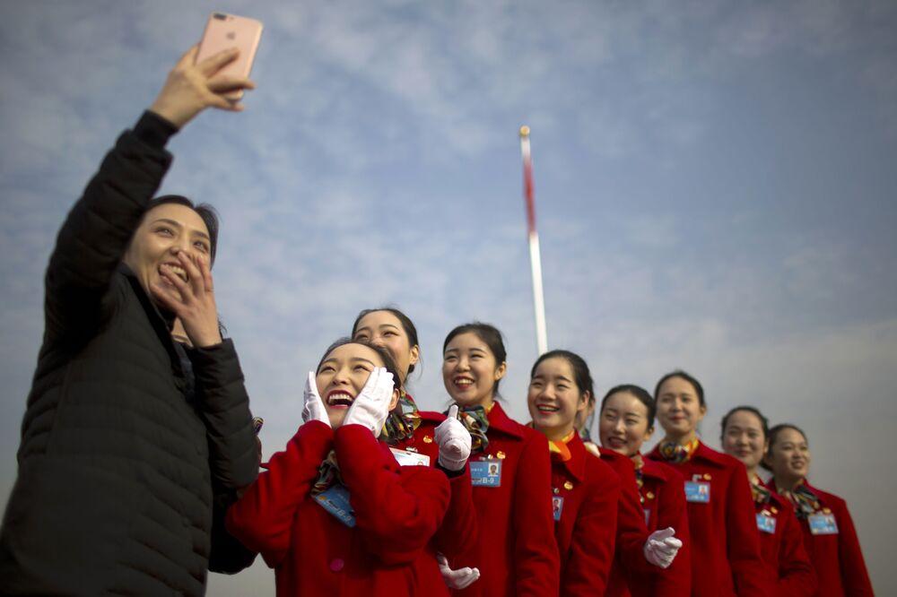 Funcionárias da indústria de turismo tiram selfie do Congresso Nacional do Povo, Assembleia Popular Nacional em Pequim