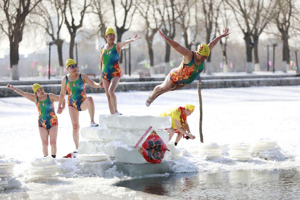 Mulher mergulha em um lago parcialmente gelado em Shenyang na província chinesa de Liaoning