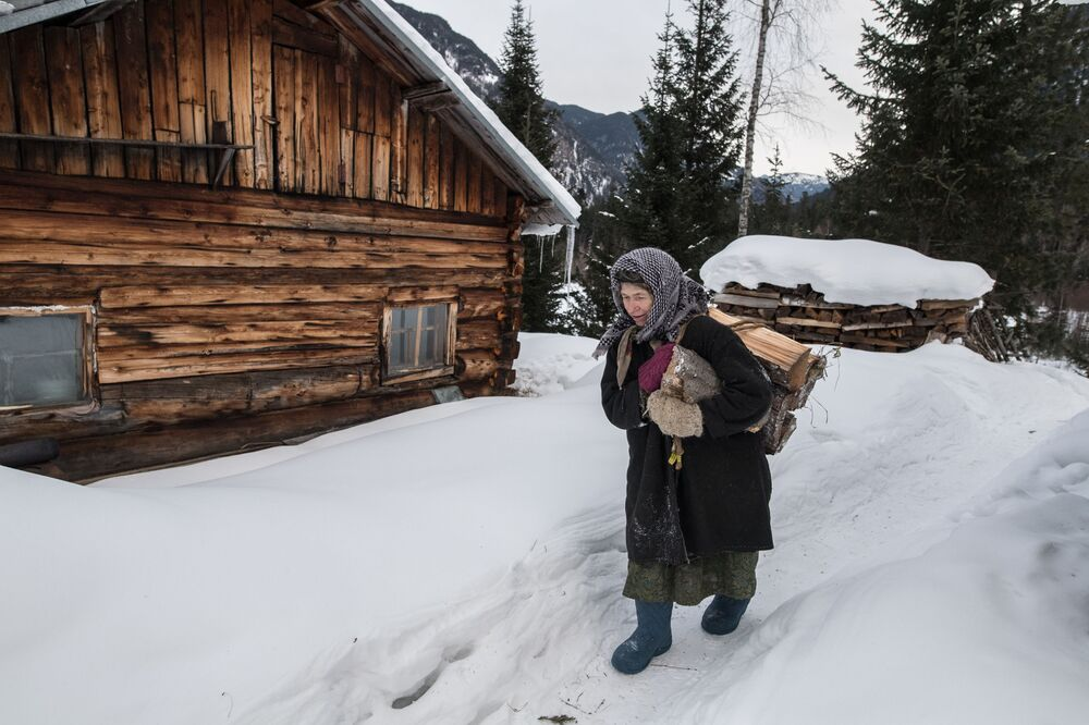 Eremita ortodoxa de rito antigo Agafia Lykova, segurando uma braçada de lenha, na região de taiga russa