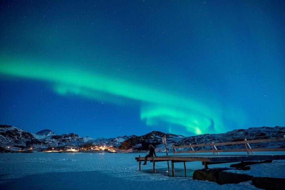 Mulher sentada no cais admirando a aurora boreal no arquipélago de Lofoten, em Noruega