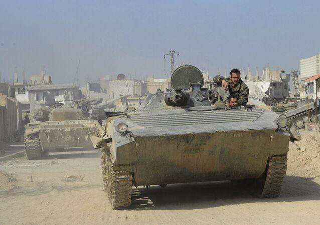 Soldados das tropas governamentais sírias em um veículo armado em Ghouta Oriental