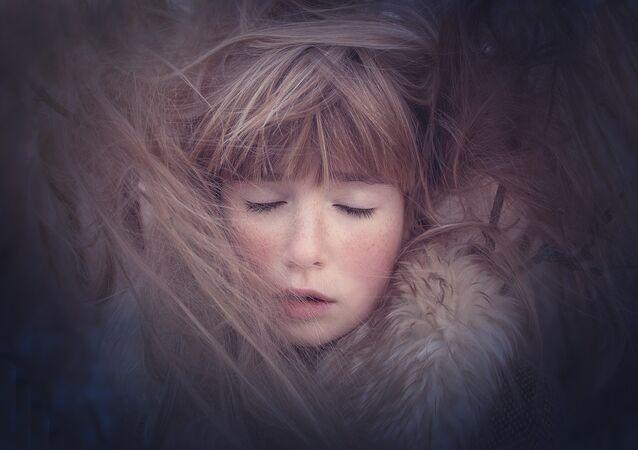 Rosto de uma menina com os olhos fechados