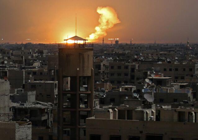 Uma foto tirada em 28 de fevereiro de 2018 mostra chamas em erupção no horizonte após um ataque relatado em al-Shaffuniyah, no enclave de Ghouta Oriental.
