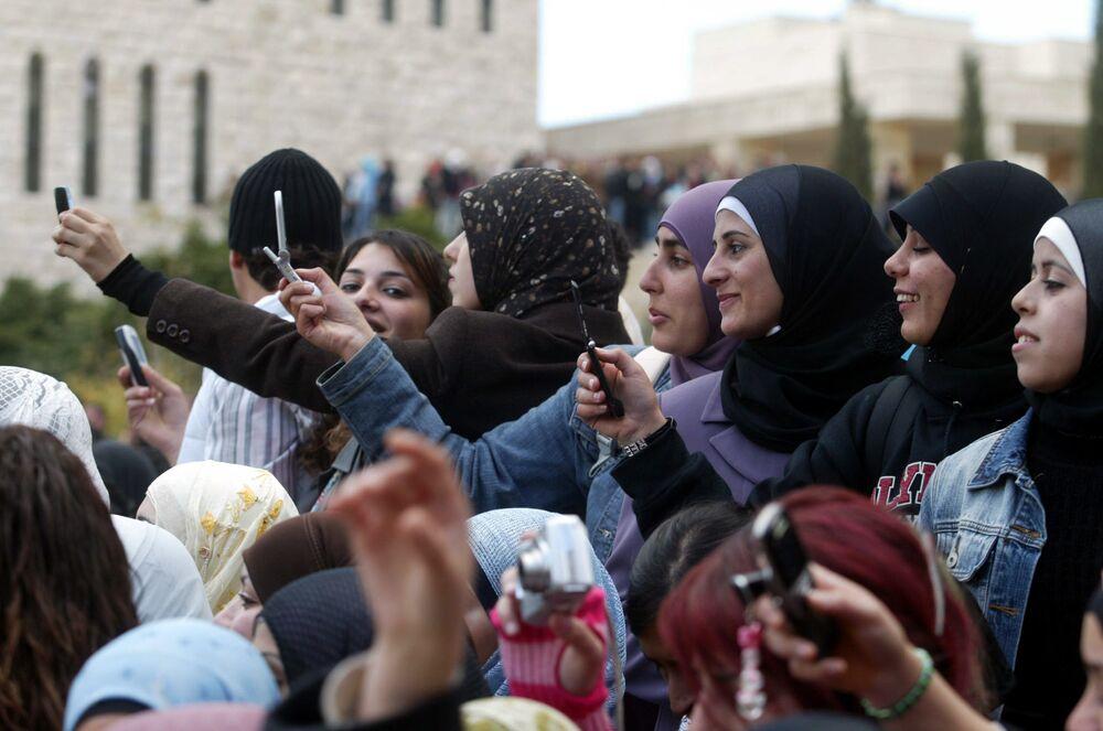 Estudantes palestinos tiram fotos do físico renomado, Stephen Hawking, que chegou à Cisjordânia para realizar uma palestra