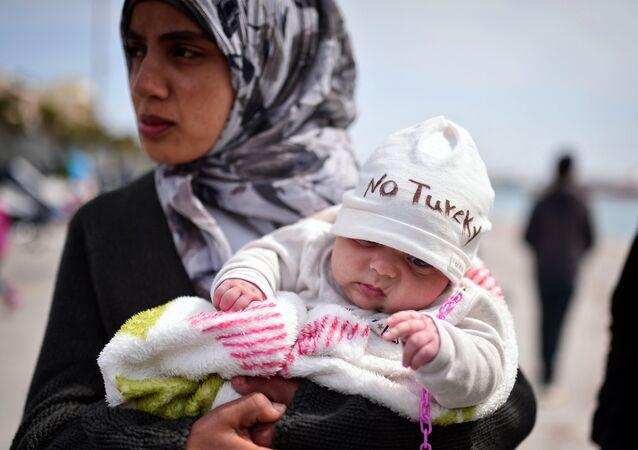 Refugiada síria segurando bebê de dois meses como refugiados e migrantes que partiram do campo de detenção de Chios, e acamparam no porto da cidade, organizando um protesto com seus filhos cantando 'No Turkey', em 3 de abril de 2016