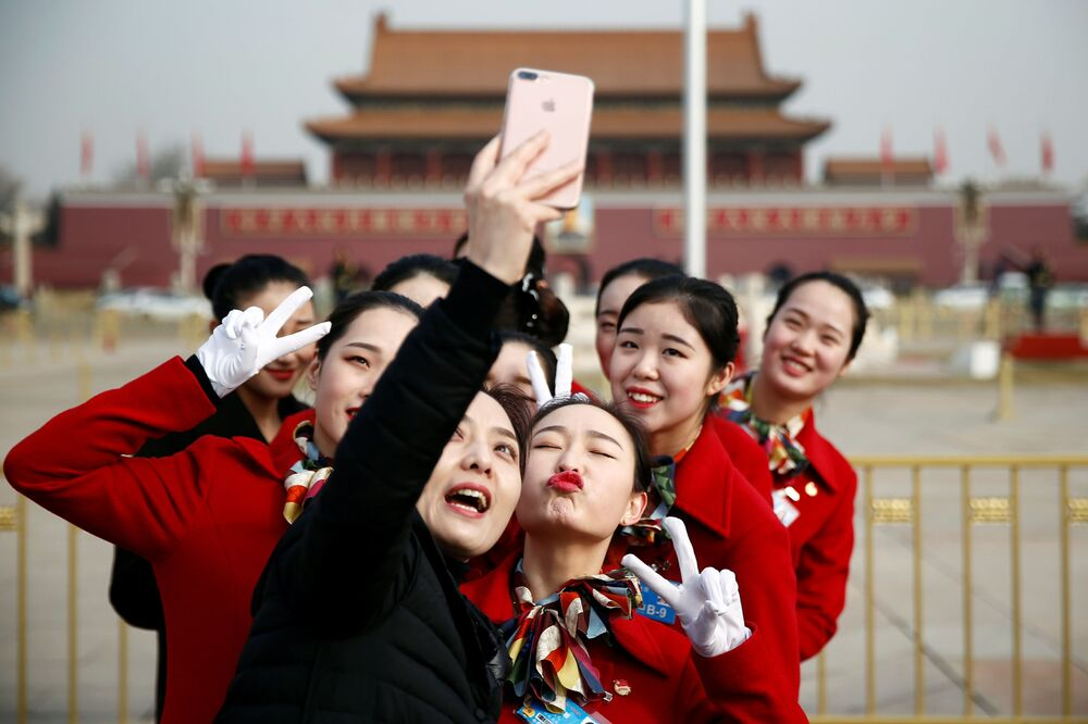 Moças da equipe de hospitalidade tiram selfie durante o Congresso Nacional do Povo, na Praça Tiananmen em Pequim, China