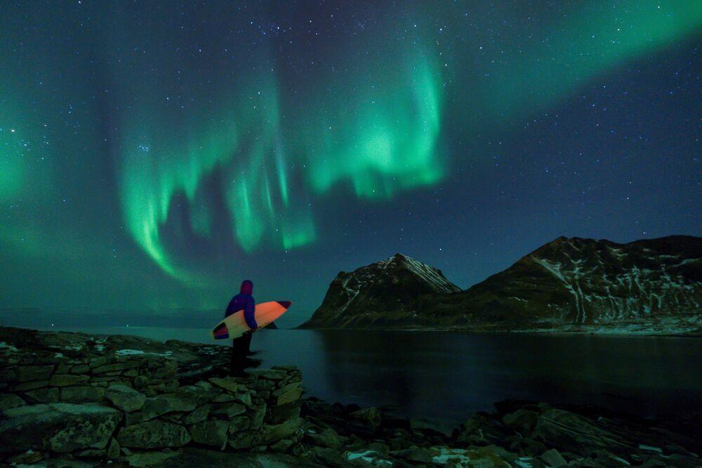 Surfista olha para aurora boreal, arquipélago Lofoten, Noruega