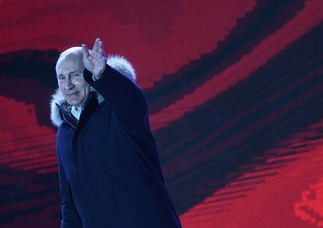 Vladimir Putin saudando pessoas durante concerto em homenagem ao quarto ano da Crimeia como parte da Rússia, na Praça Manezhnaya, Moscou