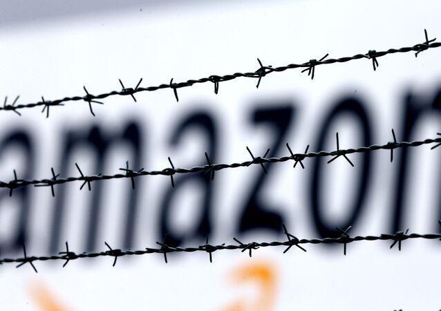 Logo da Amazon é visto por detrás de arame farpado no centro de logística de Rheinberg, na Alemanha.