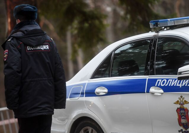 Agente federal russo perto de um carro policial