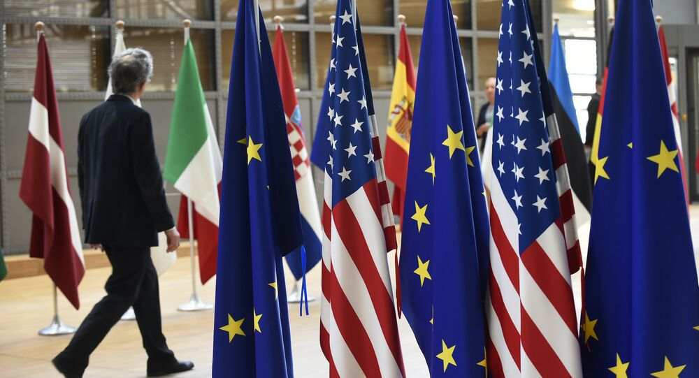 Um homem caminha perto das bandeiras dos EUA e UE na sede da União Europeia, em 15 de Maio de 2017.
