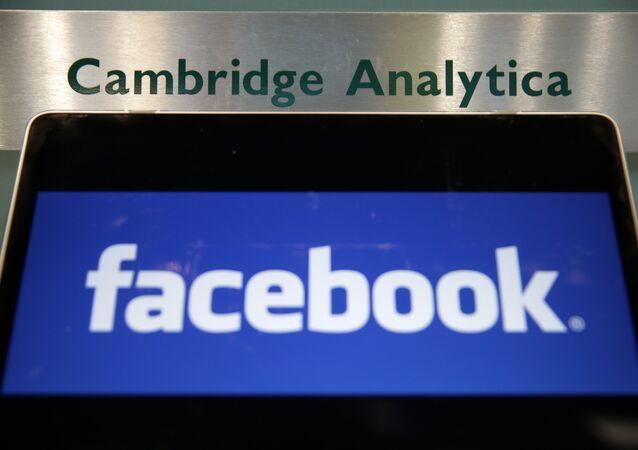 Laptop mostrando logotipo do Facebook é mantido ao lado de uma placa da Cambridge Analytica na entrada do prédio que abriga os escritórios da Cambridge Analytica, no centro de Londres.