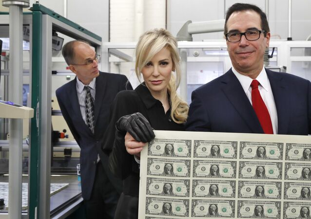 Steven Mnuchin, secretário do Tesouro dos EUA, com sua mulher Louise Linton, mostram novas notas de um dólar, sendo elas as primeiras a luzir sua assinatura e a da Tesoureira, Jovita Carranza, em 15 de novembro de 2017