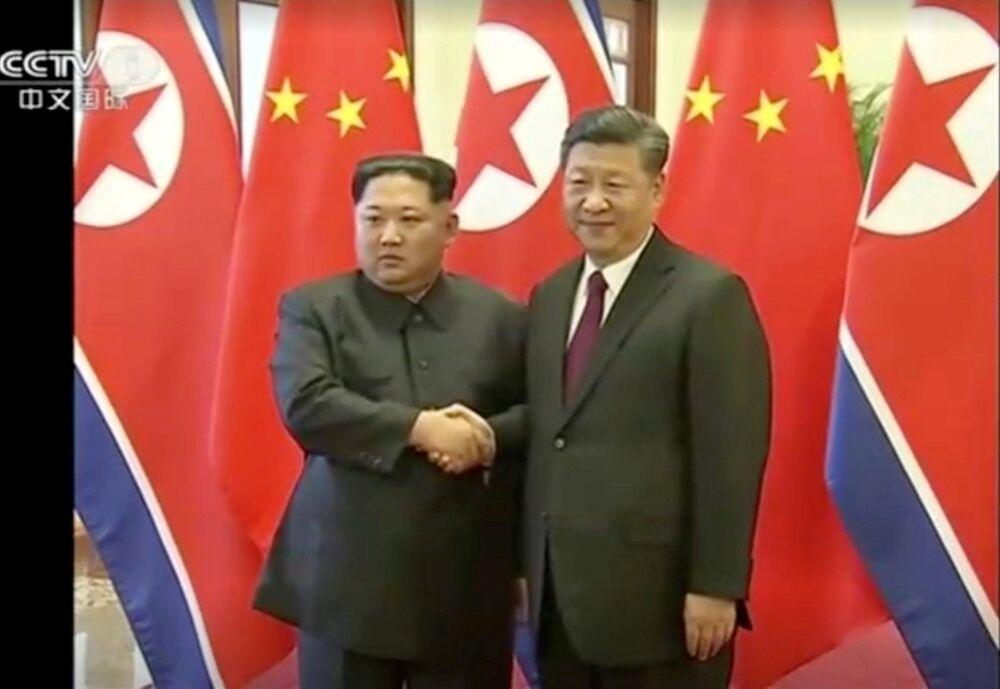 Líder norte-coreano, Kim Jong-un, aperta a mão do seu homólogo chinês, Xi Jinping, durante seu histórico encontro bilateral celebrado entre 25 e 28 de março de 2018, em Pequim
