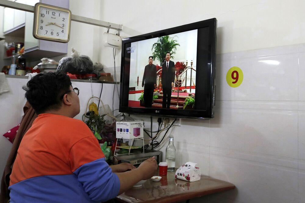 Cidadão chinês toma café da manhã ao assistir um noticiário sobre o encontro bilateral entre Kim Jong-un e Xi Jinping, em Pequim