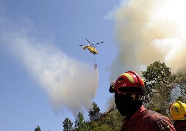 Bombeiros observam helicóptero Kamov jogando água sobre incêndio florestal em Penoita, perto de Vouzela, centro de Portugal, 23 de agosto de 2013