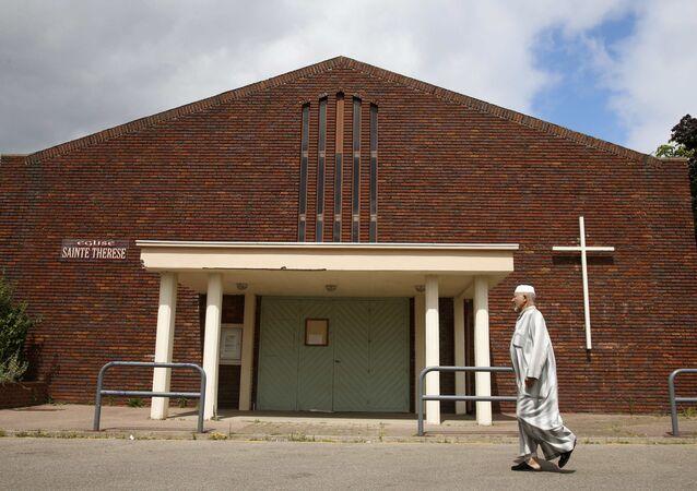 Um muçulmano passa pela igreja Sainte Therese em Saint-Etienne-du-Rouvray, perto de Rouen, na Normandia, França
