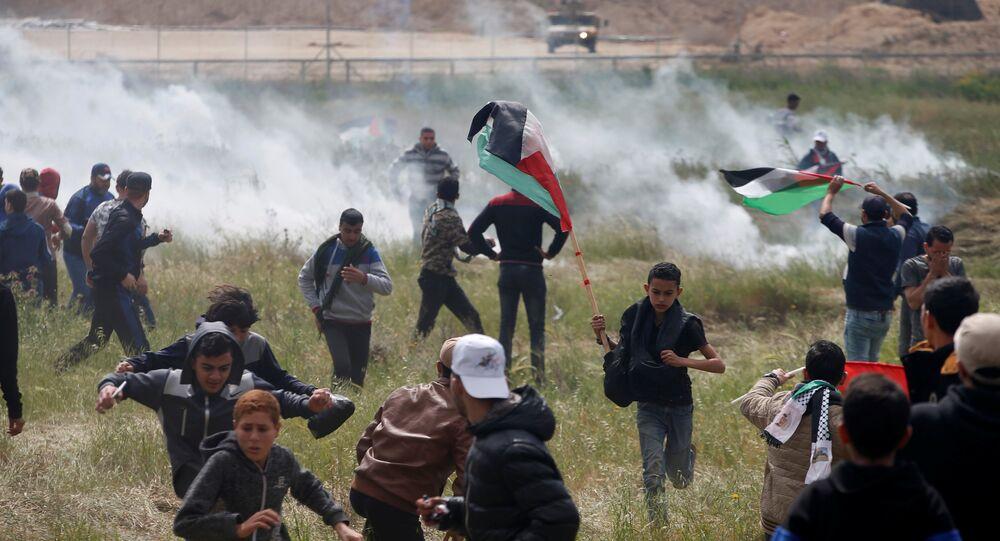 Palestinos correm de gás lacrimogênio atirado por tropas israelenses durantes protesto na Faixa de Gaza.