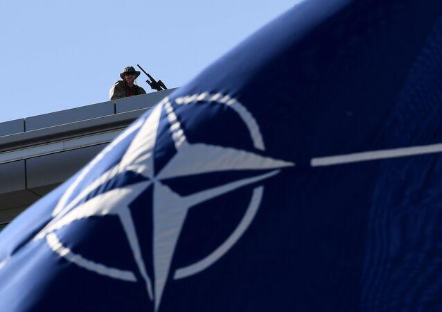 Bandeira da OTAN com um militar em fundo