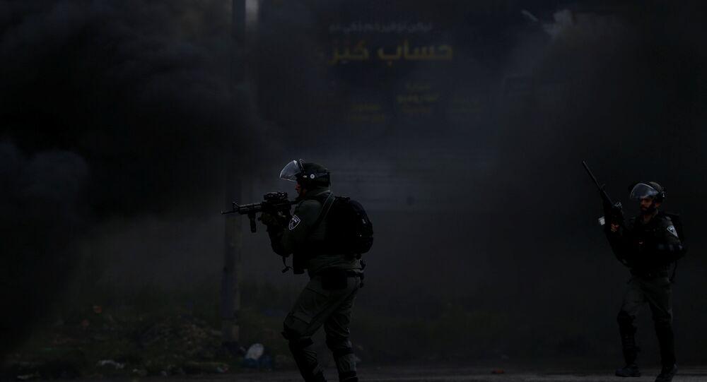 Policial israelense aponta arma contra manifestantes palestinos, 30 de março de 2018