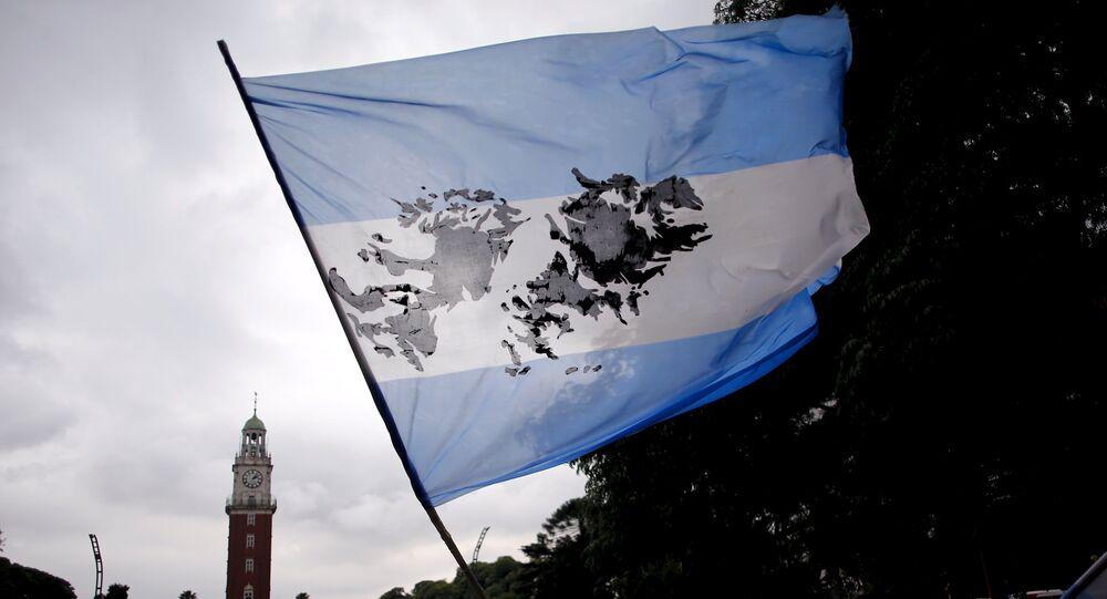 Homem segurando bandeira argentina com imagem das ilhas Malvinas (foto de arquivo)