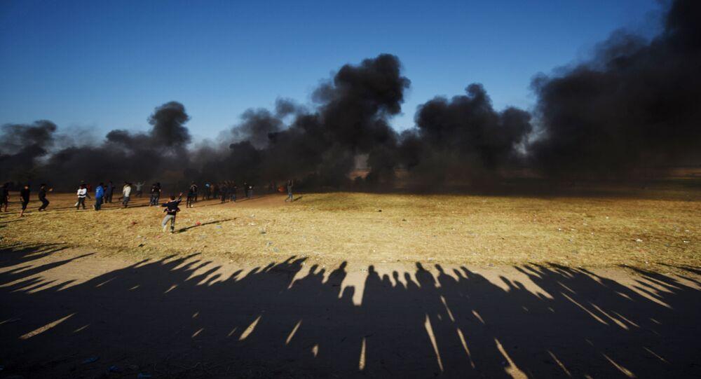 Manifestantes palestinos durante os confrontos com soldados israelenses na fronteira entre a Faixa de Gaza e Israel