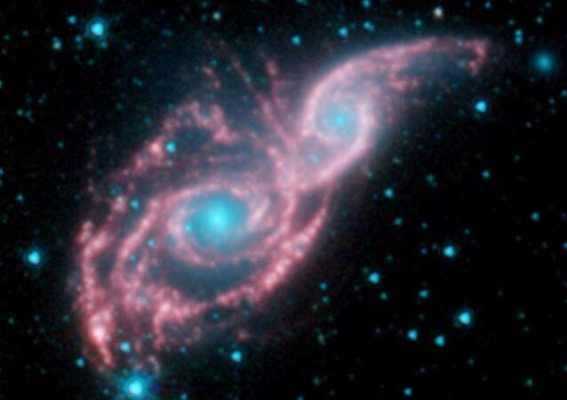 Dois olhos azuis com uma máscara iluminada, nesta foto, são o produto da fusão das galáxias NGC 2207 e IC 2163