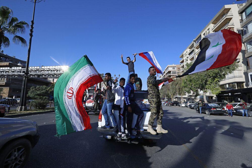Manifestastes contra os ataques da coalizão internacional na Síria agitando bandeiras da Síria, Irã e Rússia