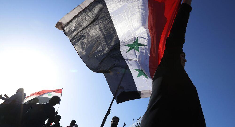 Participantes de uma manifestação contra os ataques aéreos da coalizão internacional na Síria agitam bandeiras da República Árabe da Síria