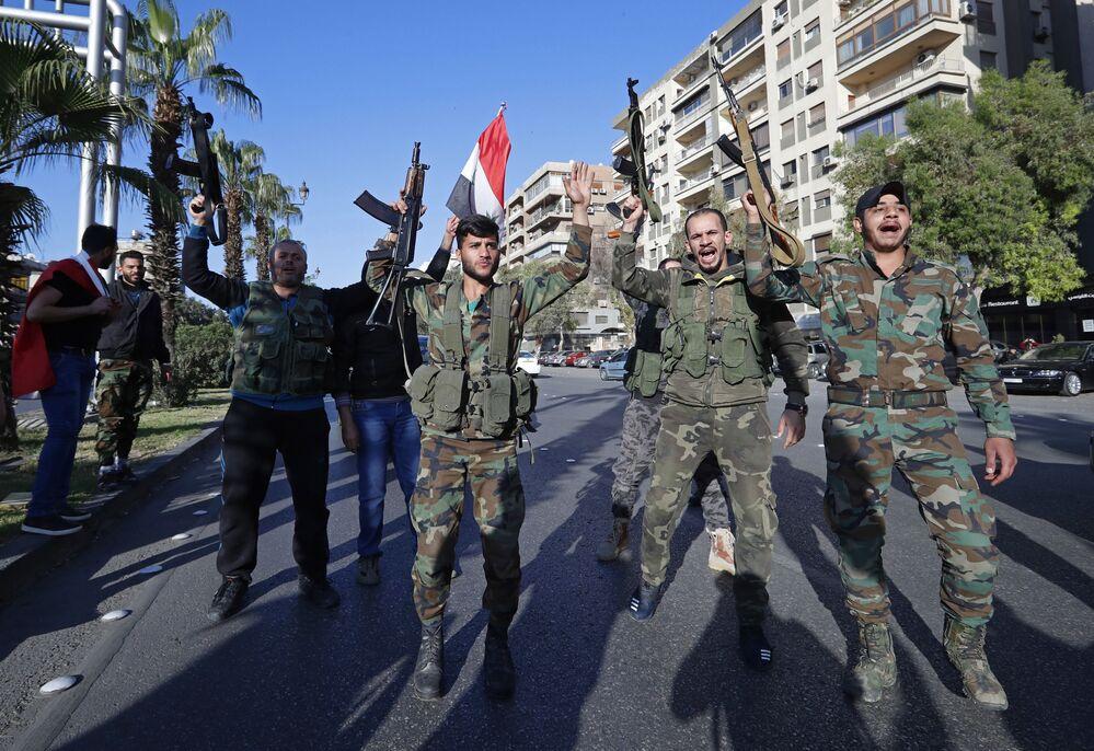 Militares do exército sírio participam de uma manifestação contra os ataques aéreos da coalizão internacional