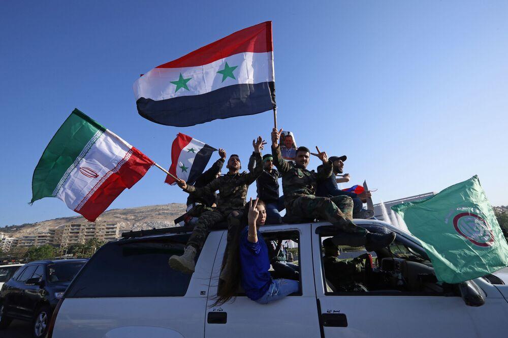 Cidadãos sírios agitam bandeiras da Síria durante uma manifestação contra os ataques aéreos da coalizão liderada pelos EUA