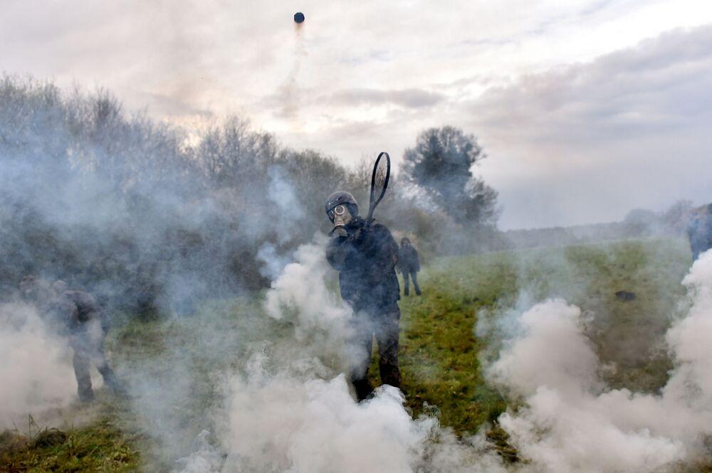 Manifestante usa raqueta para lançar uma botija de gás lacrimogéneo durante as confrontações com a polícia na sequência de liquidação do campo ecológico em Notre-Dame-des-Landes, na França