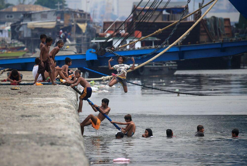 Crianças se banham em água poluída da baía de Manila durante o calor extremo nas Filipinas