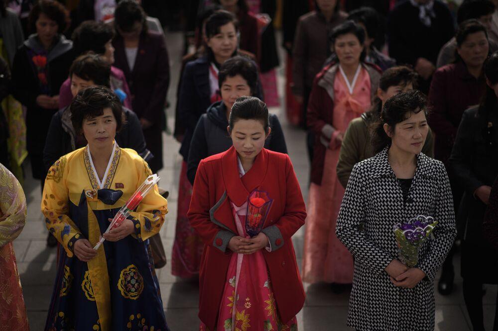 Mulheres depõem flores nos monumentos dos líderes norte-coreanos Kim Il-sung e Kim Jong-il, Pyongyang, 15 de abril de 2018