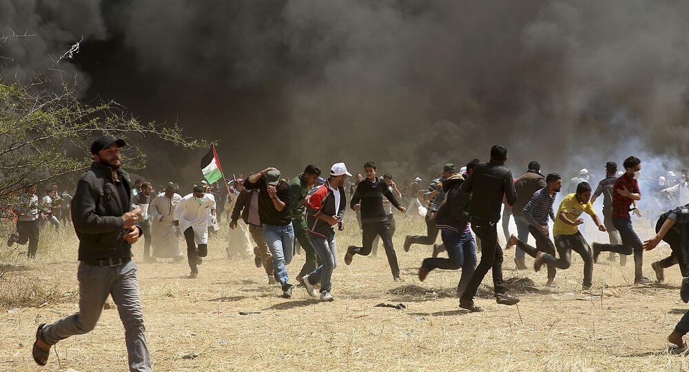 Manifestantes palestinos correm para se proteger de bombas de gás lacrimogêneo disparadas por soldados israelenses durante confrontos em Gaza (arquivo)