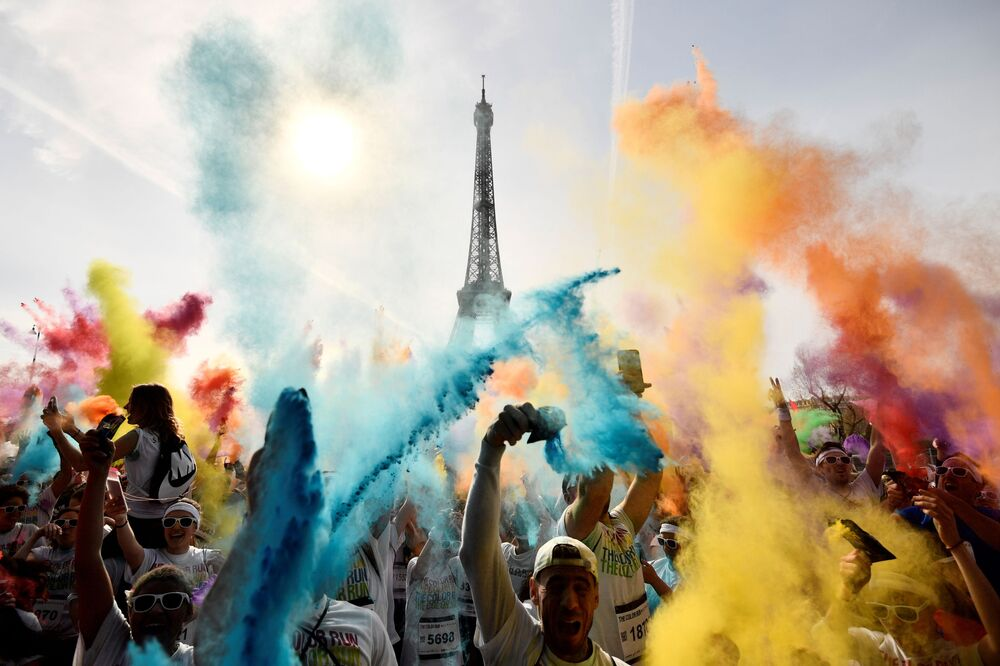 Participantes da corrida Color Run 2018 celebram a chegada ao fim em frente à Torre Eiffel.